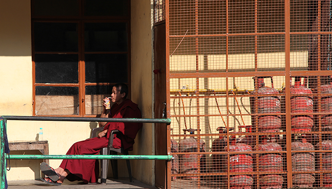 monk sipping a fizzy drink near gas bottles